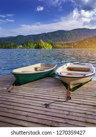 Iconic Bled scenery. Traditional wooden boats Pletna at lake Bled, Slovenia, Europe. Wooden boats with Pilgrimage Church of the Assumption of Maria on the Island on Lake Bled, Slovenia
