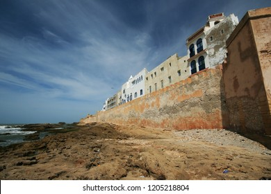 Iconic blue shuttered, white washed buildings, showing wild, barren Atlantic coast, Essaouira, Morocco, North Africa