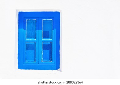 Iconic blue wooden window against clear white wall. Typical view for Greek islands, Greece