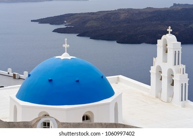 Santorini's iconic blue-domed church with island and ocean as background, one of the famous tourist spot in Oia, Santorini Greece.