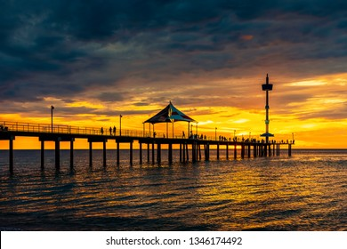 Iconic Brighton jetty with fishermen silhouettes at sunset, South Australia