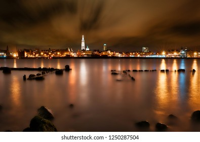 Iconic cityscape over Antwerp. This view is marvelous. The long exposure give movement in the clouds. The cathedral draws the attention of our eye. The river Scheldt has a 'milky' look.