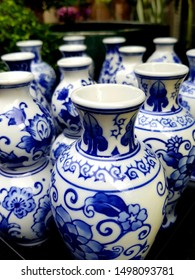 An iconic collection of traditional Delft Blue pottery vases on display in Amsterdam's main shopping area.