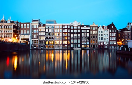 Iconic Damrak Amsterdam street waterfront at the evening shot with long exposure during sunset