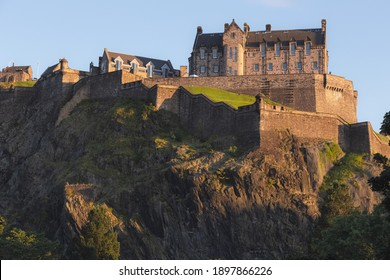 The iconic Edinburgh Castle in golden light perched atop Castlehill on a summer evening as seen from Princes Street Gardens, Scotland.