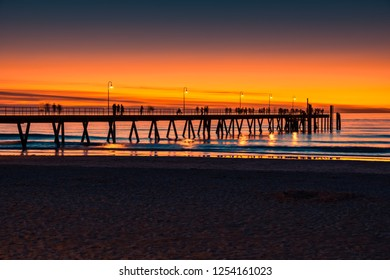 Iconic Glenelg beach with people's silhouettes on jetty at dusk, South Australia