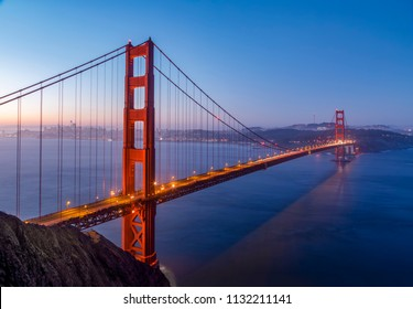 The iconic Golden Gate Bridge is backed by San Francisco Bay and the City of San Francisco just before sunrise.