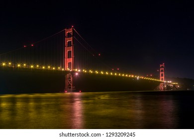The iconic Golden Gate Bridge spans the narrows leading into California's San Francisco Bay from the Pacific Ocean at night.