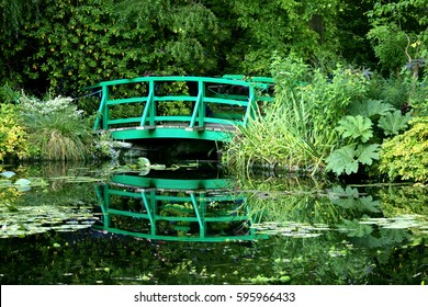 The iconic green Japanese bridge reflecting in the water lilies pond in Claude Monet's Garden of Giverny, Normandy, France