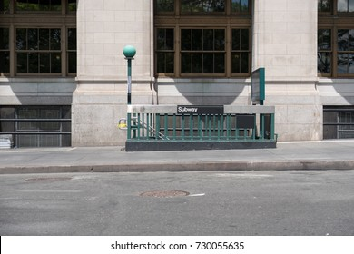 Iconic green lamps marking entrance to New York subway. Steps on sidewalk that lead to entrance of New York City subway station. Public train satiation entrance in lower Manhattan, NYC.