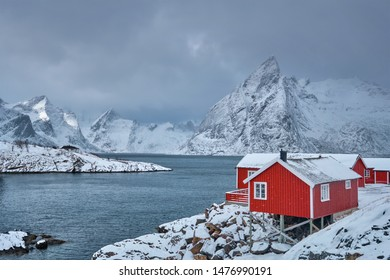 Iconic Hamnoy fishing village on Lofoten Islands, Norway with red rorbu houses. With falling snow in winter.
