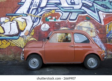 iconic italian small red car against contemporary graffiti background rome italy