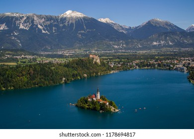 Iconic landscape view of beautiful  St. Marys Church of Assumption on small island,lake Bled in Slovenia .Bled Castle on background. Summer scene travel Slovenia concept. Tourist popular attraction