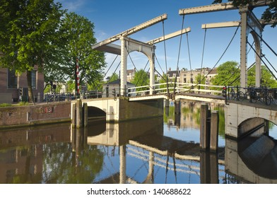 Iconic Magere Brug (1671) delicate wooden bridge reflected in the Amstel canal Amsterdam.