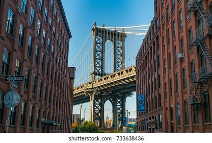 The Iconic Manhattan Bridge Viewed From Dumbo, Brooklyn, between two brick buildings with the Empire State building framed in the bottom (New York, September 2017).
