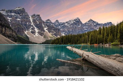 Iconic Moraine Lake in Alberta Canada during summer time tourist season with turquoise, aqua water below and pink sunrise.
