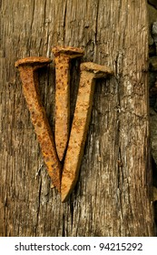 Iconic photo of three rusty spikes lying on a wooden beam. (Symbolic image of Jesus' crucifixion.)