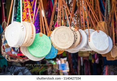 Iconic rattan hand bags hanging for souvenir at a street shop in Ubud market of Bali island, Indonesia.