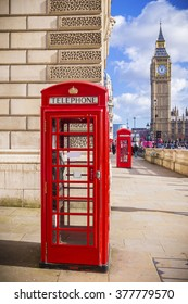 Iconic Red British telephone box with Big Ben on a sunny afternoon with blue sky - London, UK