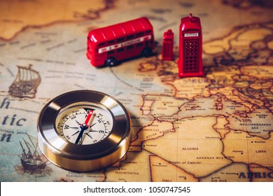The iconic red bus and Big Ben miniature with compass on the map of London, UK. Concept of travel.