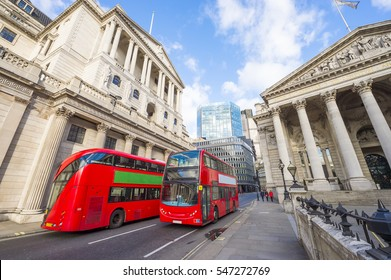 Iconic red double-decker buses passing in front of the Bank of England in a scenic cityscape of the traditional financial district of The City in London, England