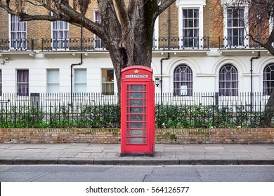 Iconic red London phone booth in front of a block of residential building and a big tree in the Paddington area