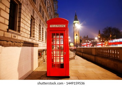 Iconic Red Telephone Booth and Big Ben Clock Tower at Night. Nobody present.