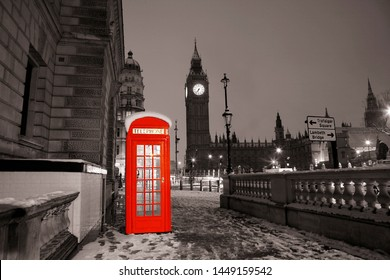 Iconic Red Telephone Booth and Big Ben Clock Tower on a Snowy Night. Nobody present.