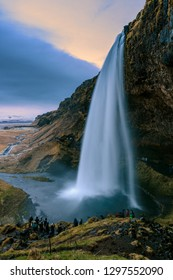 The Iconic Seljalandsfoss Waterfall In Iceland. There are unrecognizable tourist people with motion blur in the foreground.