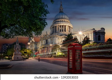 The iconic St. Pauls Cathedrale in London, UK, a major tourist attraction, just after sunset with blurred traffic and a red telephone booth