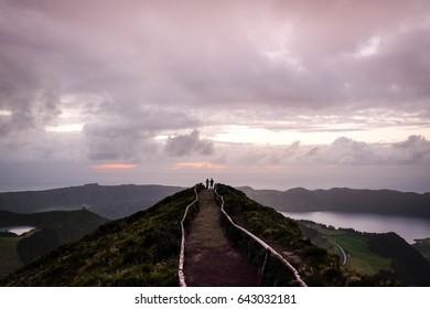 Iconic sunset view on azorean Sao Miguel Island with man and woman - miradouro da boca do inferno