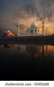 The iconic Taj Mahal rear seen riverside with fiery sunset sky beautifully reflected in the calmly flowing Jamuna river in Agra, India in the evening. Vertical copy space