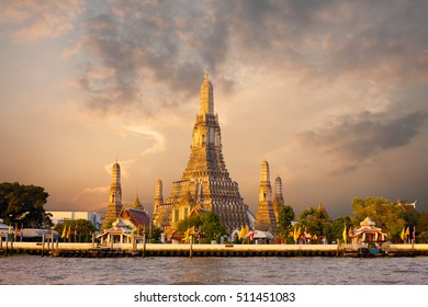 The iconic Temple of Dawn, Wat Arun, along the Chao Phraya river with a colorful red sky at morning sunrise in Bangkok, Thailand