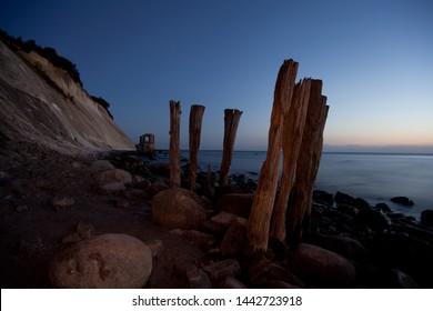 Iconic timber piles and old watchhouse at coastline of Ruegen chalk cliff at blue hour