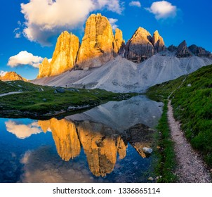 Iconic Tre Cime di Lavaredo and reflection during beautiful sunset