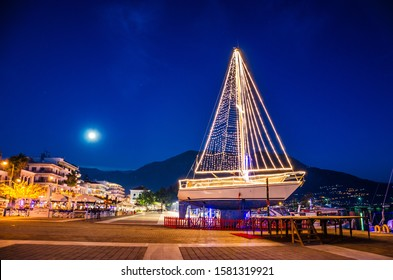 Iconic view of a decorated wooden sailing boat during Christmas period against a starry night