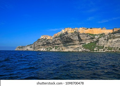 Iconic village of Bonifacio upon the limestone cliffs with colored houses seen from the sea with far away, the Madonetta lighthouse, Bonifacio, Corsica island, France