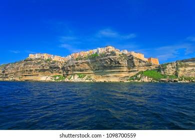 Iconic village of Bonifacio upon the limestone cliffs with colored houses seen from the sea, Bonifacio, Corsica island, France