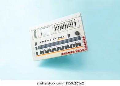 Iconic vintage Japanese analog drum-machine/ groove box, levitating on blue background. electronic music concept