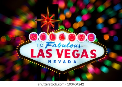 Iconic Welcome to Fabulous Las Vegas sign with multiple blurry lights in the back