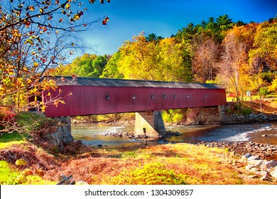 A iconic west cornwall covered bridge spanning the Houstanic River in Connecticut during the new england autumn.