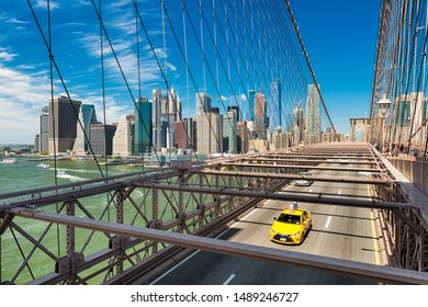 Iconic yellow taxi on the Brooklyn Bridge with the Manhattan skyline in the background, New York
