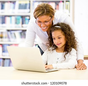 ICT teacher with a young student using the computer
