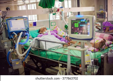 ICU room in a hospital with medical equipments and patient.