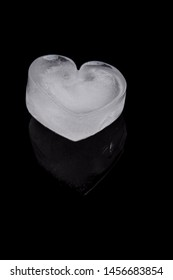 icy cold heart shaped ice cube on a black background