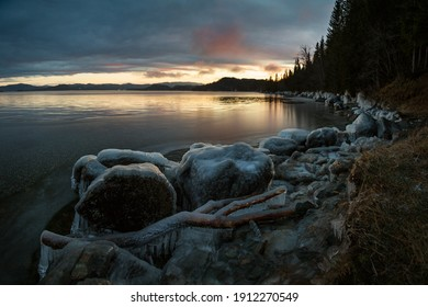 Icy frozen shore of the lake in sunset time. Jonsvatnet lake near Trondheim in Norway. Beautiful sunset colors on the sky and clouds. Ice patterns and texture. Frosty winter time.