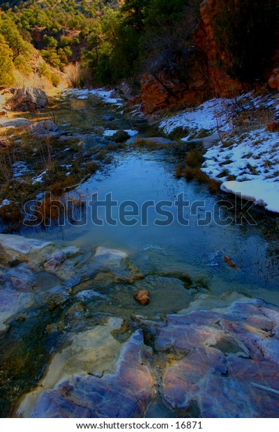 Icy mountain stream in late winter sunrise reflects the blue of the skies above.