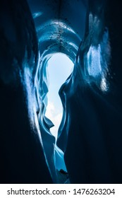 Icy pit of an ice cave, looking up at the sky from deep within a curvy walled crevasse on the Matanuska Glacier in Alaska.