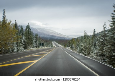 Icy road conditions in Canadian Rockies with yellow midde lane and snowy mountain in background with motion blur