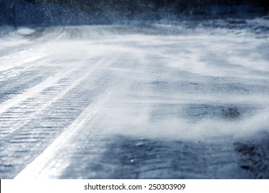 Icy Road with Drifting Snow Closeup. Dangerous Icy Road Conditions.
